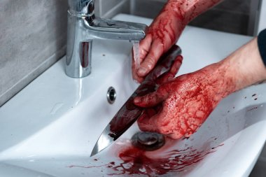 cropped view of killer washing knife in sink after murder