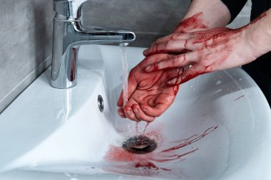partial view of man washing bleeding hands in sink