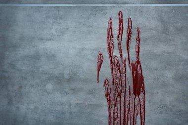 red bloody hand print on grey textured surface