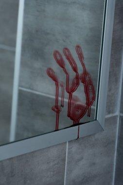 selective focus of bloody handprint on mirror in bathroom