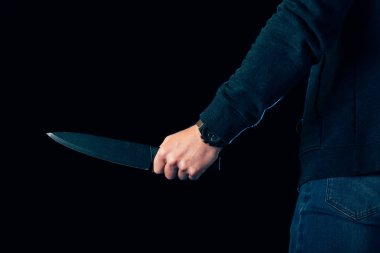cropped view of killer holding knife isolated on black