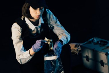 investigator in uniform putting dollar banknote in ziploc bag isolated on black