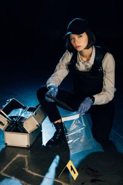 investigator holding knife and ziploc bag at crime scene