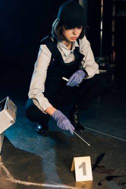 investigaror in gloves holding test tube and swab at crime scene