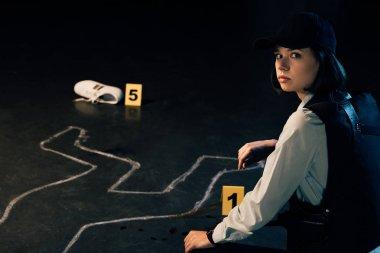 investigator sitting near chalk outline at crime scene
