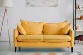 Photo spacious, light living room with bright yellow sofa, floor lamp and rack