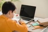 Schüler macht Hausaufgaben, während er am Schreibtisch neben Laptop mit leerem Bildschirm sitzt