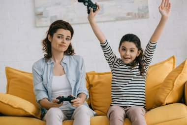 KYIV, UKRAINE - APRIL 8, 2019: Cheerful daughter showing yes gesture while sitting near upset mother holding joystick stock vector