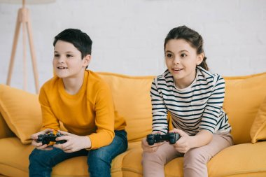 KYIV, UKRAINE - APRIL 8, 2019: Focused brother and sister playing video game with joysticks while sitting on sofa at home stock vector