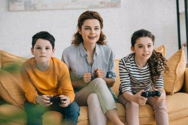 KYIV, UKRAINE - APRIL 8, 2019: Cheerful woman sitting on sofa near children playing video game with joysticks stock vector