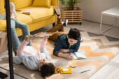 Fotografie adorable kids lying on floor at home and doing schoolwork together