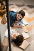 Fotografie Hochwinkelansicht von niedlichen Bruder und Schwester auf dem Boden liegend und Hausaufgaben machen