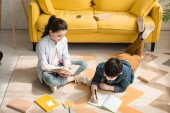 Fotografie high angle view of adorable kids doing schoolwork on floor at home