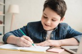 cheerful boy writing in notebook while sitting at desk and doing homework