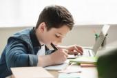 imádnivaló figyelmes fiú írás-ban jegyzetfüzet és használ laptop rövid idő csinálás lecke