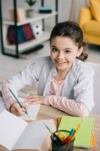 Fényképek vidám iskolás írásban notebook és mosolyogva a kamera mindeközben házi feladatot