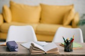 selective focus of wooden desk with open book, copy books, pencil case and stationery