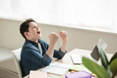 excited schoolboy showing yes gesture while sitting at desk and doing homework
