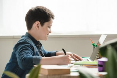 smiling boy writing in notebook and using laptop while doing schoolwork at home