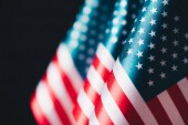 selective focus of usa national flags isolated on black, memorial day concept