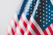 selective focus of united states of america national flags isolated on grey, memorial day concept