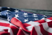 folded american flag on grey background, memorial day concept