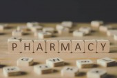 selective focus of pharmacy inscription on cubes surrounded by blocks with letters on wooden surface isolated on black