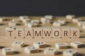 selektivní zaměření slov týmových prací z krychlí obklopených bloky s písmeny na dřevěném povrchu izolovaným na černém