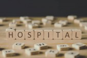 selective focus of cubes with word hospital surrounded by blocks with letters on wooden surface isolated on black