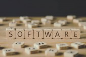 selective focus of software lettering on cubes surrounded by blocks with letters on wooden surface isolated on black