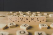 selective focus of cubes with word romance surrounded by blocks with letters on wooden surface isolated on black