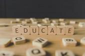 selektivní zaměření slova vzdělávat se v kostkách obklopených bloky s písmeny na dřevěném povrchu izolovaně na černém
