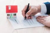 částečný pohled na vytvoření realtora v dohodě o půjčce blízko modelu domu na dřevěné desky