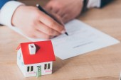 Photo cropped view of businessman writing in loan agreement near house model on wooden tabletop