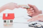 částečný pohled na obchodníka, který bere peníze od klienta v blízkosti modelu domu na desky