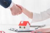 oříznutý záběr realtora potřásaje si rukama s klientem poblíž modelu domu na desky