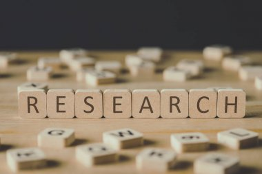 selective focus of word research made of cubes surrounded by blocks with letters on wooden surface isolated on black