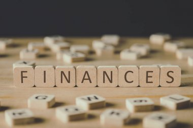 selective focus of finances inscription on cubes surrounded by blocks with letters on wooden surface isolated on black