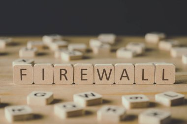 selective focus of firewall inscription on cubes surrounded by blocks with letters on wooden surface isolated on black