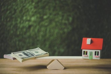 dollar banknotes and house model balancing on seesaw on green background