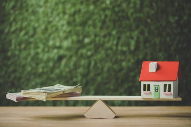 house model and dollar banknotes balancing on seesaw on green background