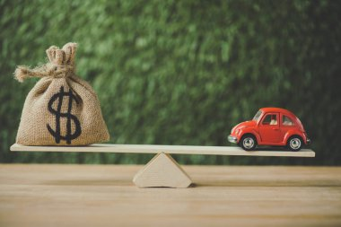 toy car and money bag with dollar sign balancing on seesaw on green background