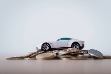 miniature car on metal coins on wooden surface isolated on grey