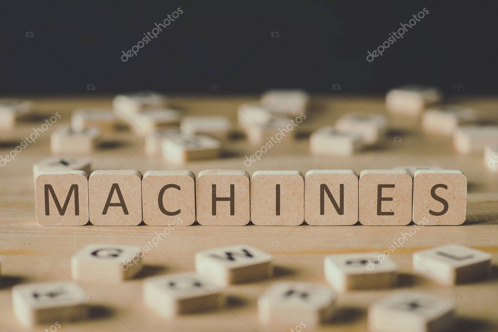 selective focus of machines lettering on cubes surrounded by blocks with letters on wooden surface isolated on black