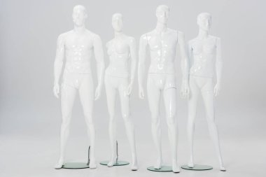 White plastic mannequins in row on grey stock vector