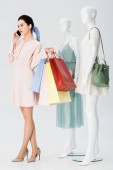 young woman with shopping bags talking on smartphone near mannequins on grey