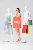 hübsche junge Frau mit Verkauf Schriftzug auf Einkaufstasche neben Schaufensterpuppen auf grau