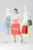 szép fiatal nő, eladó betűkkel a bevásárló táska közelében mannequins a szürke