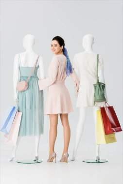 Beautiful young woman holding hands with mannequins with shopping bags isolated on grey stock vector