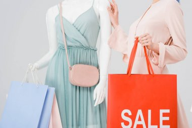 Cropped view of young woman holding shopping bag with sale word near mannequin isolated on grey